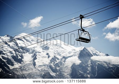 Silhouette of a chairlift in Mont Blanc Massif, in the background is Mont Blanc peak, Alps, Chamonix, France