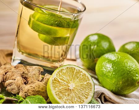 Healthy detox drink with ginger . On wooden boards glass with green tea and mint. A mint ginger drink number twenty six with half lime and napkin. Country life. Light background. Slanted angle.