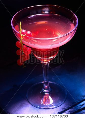 Alcohol cocktail on black background. Pomegranate cocktail decoration red currant branch. Cocktail card