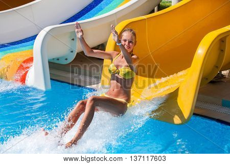 Child on water slide at aquapark hands up. There are some water slides with flowing water in aqua park. Girl jumps in water. Summer water park holiday. Outdoor.