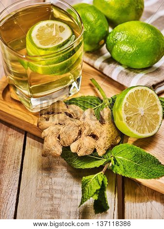 Healthy detox drink with ginger . On wooden boards glass with green tea and mint. A mint ginger drink number twenty five with half lime and napkin. Country life. Light background.