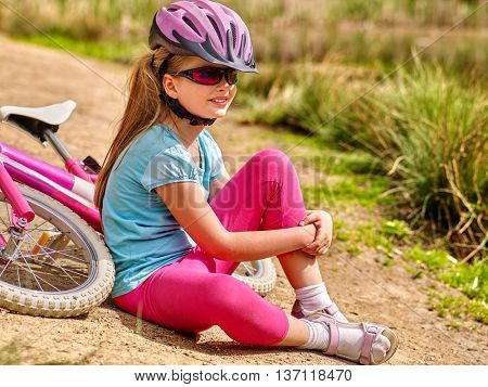 Bikes bicycle child . Happy child sitting on road near bicycles. Cycle racing concept. Child wearing bicycle helmet.