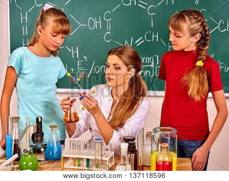 Child and teacher holding flask and chemistry model in chemistry class.