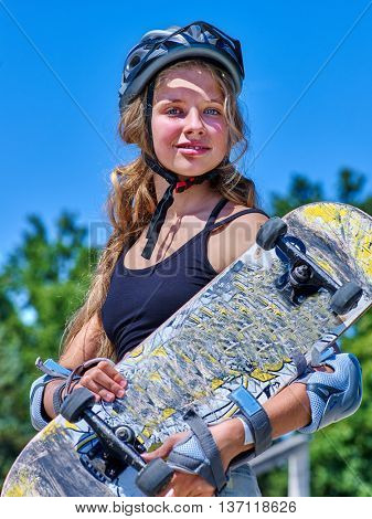 Teen skateboarding with her skateboard outdoor. Girl holding skateboard.