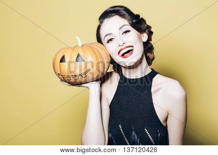 Smiling woman with beautiful face and retro hairdo and red lips holding pumpkin in studio on yellow background. Halloween concept