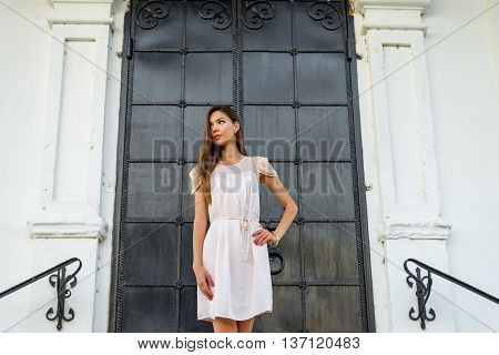 Beautiful brunette girl in a black metal door on the stairs poses. Fashion style. Tanned woman in pink dress outdoors resting on a background of the old gothic castle church concept