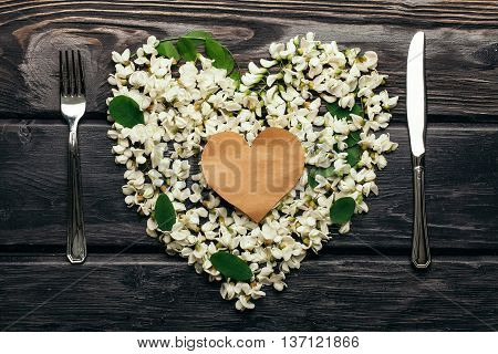 Empty note on white acacia blossoming flower petals arranged in heart shape with fork and knife on dark wooden background