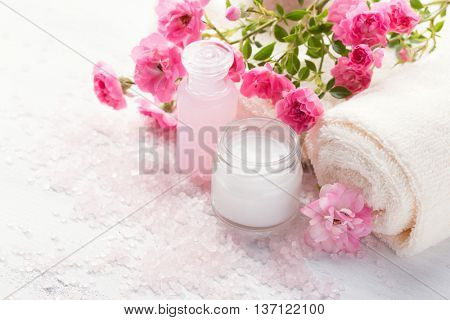 Spa setting with   branch of  small  pink roses.  Selective focus