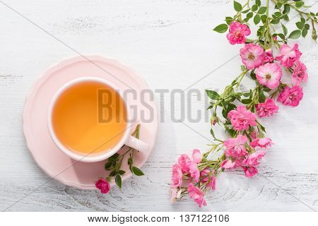 Cup of tea and branch of small pink  roses on rustic table.