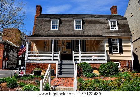 Alexandria Virginia - April 13 2014: Colonial 1724 William Ramsay House with front porch. gambrel roof and garden is now the visitor center *