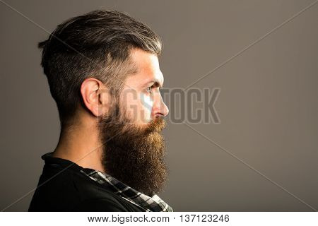 young handsome bearded man with long beard moustache and brunette hair with emotional face in studio on grey background copy space