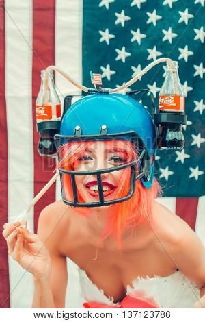 Ukraine Kyiv - July 27 2016:young patriotic sexy woman with pretty smiling face and orange hair in football drink helmet with coca cola bottles and white dress on american flag background celebrating independence day usa