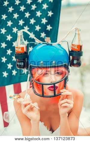 Ukraine Kyiv - July 27 2016: young patriotic sexy woman with pretty face and orange hair in football drink helmet with coca cola bottles on american flag background celebrating independence day usa