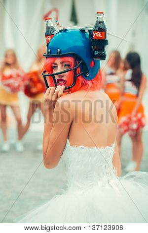 Ukraine Kyiv - July 27 2016: young patriotic sexy woman with pretty face and orange hair in soccer drink helmet with coca cola bottles and american flag celebrating independence day usa