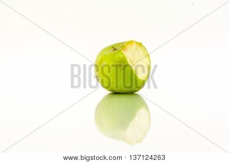 Bitten green apple with reflection on a white background