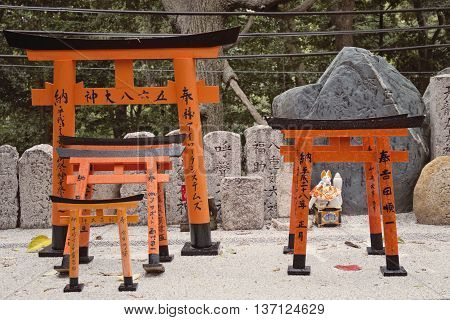 KYOTO, JAPAN - APRIL 29, 2016: Miniature torii gates at Fushimi Inari shrine in Kyoto, Japan. Old Kyoto is a UNESCO World Heritage site and was visited by almost 1 million foreign tourists in 2016.