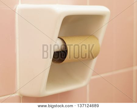 White ceramic tissue paper holder with empty tissue paper and pink tile in the background