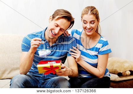 Happy couple - woman hugging her husband who holding gift box and baby shoe
