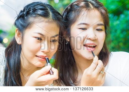 Make-up Friend Applying Powder With A Brush On Asian Model's Cheeks At  Cafe Park