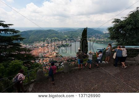 BRUNATE, ITALY - MAY 2016: Tourists on observation deck overwatch Como Lake, Aerial View of Cernobbio and Tavernola from viewpoint Brunate Funicolare, Italy. Cernobbio is a comune (municipality) in the province of Como, Lombardy, northern Italy