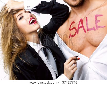 happy couple of young pretty woman with long hair and red lips and handsome sexy man with red lipstick text sale on bare muscular chest in shirt and black jacket isolated on white background