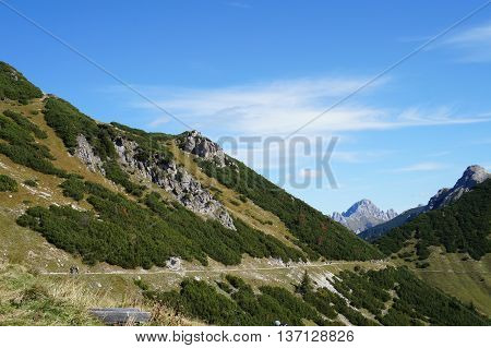 long hiking trail at a mountain in background the peaks of the Tannheim Mountains many hikers on a sunny day in October