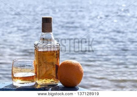 Bottle tequila and tumbler with Orange on shore of lake