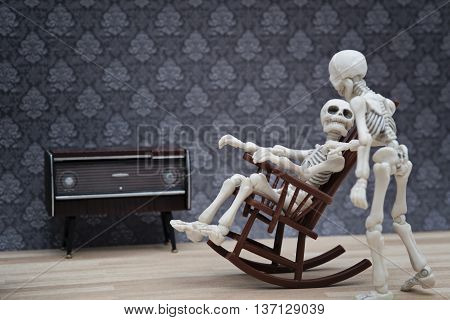 A skeleton talking with other skeleton on a rocking chair