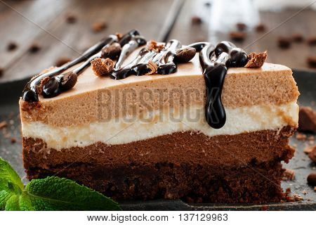 piece of layered cake with chocolate topping close-up on black plate, blurred wooden background