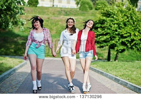 Three Happy Girls In Short Shorts And Wreaths On Heads Walking Down The Avenue Holding Hands. Bachel