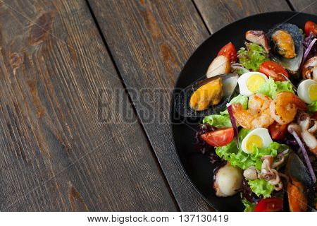 Seafood salad plate on wood half image copyspace. Portion of salad with grilled shrimps, mussels and octopus on side of picture on wooden background with free space