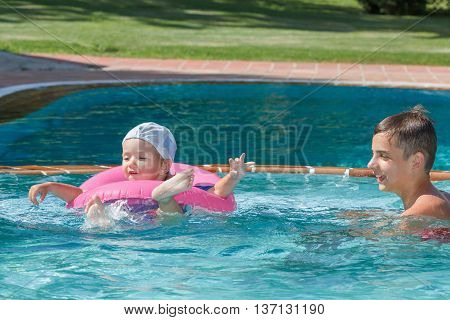 Two brothers playing in the pool on a summer's day holiday