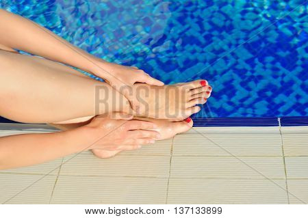Woman Legs With Red Nails Near The Pool