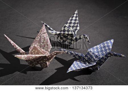 Three cranes origami in a dark room