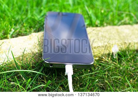 Phone detail with white USB cable on grass