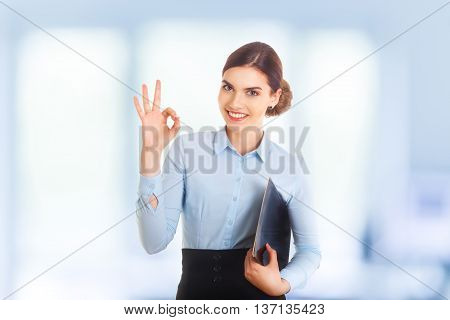 Happy smiling beautiful young businesswoman showing okay gesture. With blank copyspace area for text or slogan.