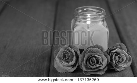 black and white roses and Glass candle On the old wooden table condolence Background