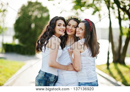 Three happy girls in short shorts and white shirts posed on road at park on bachelorette party