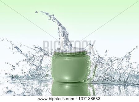 Green jar of moisturizing cream stays on the water background with big water splashes around