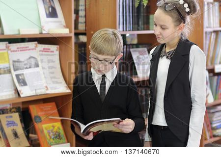 pupil in black jacket and sunglasses and schoolgirl read book on background of shelves with books
