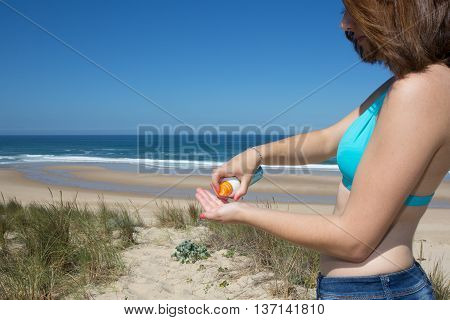 Girl Putting Sun Protection Cream At The Beach