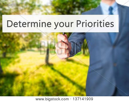 Determine Your Priorities - Businessman Hand Holding Sign
