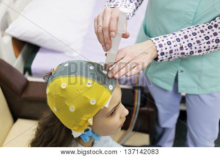 Girl before procedure electroencephalography, nurse using syringe introduces special gel for electrodes located in cap of electroencephalogram