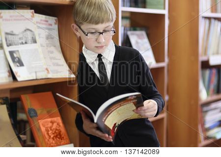 pupil in black jacket and sunglasses read book on background of shelves with books