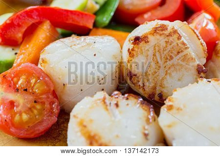 Cooked scallops with vegetables.