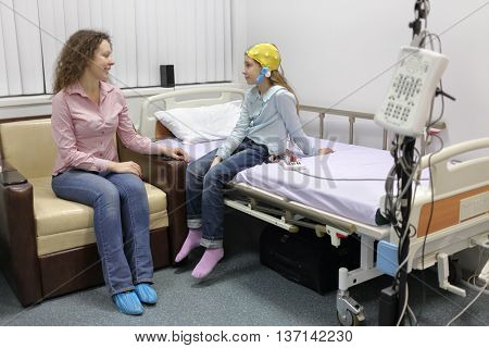 mother sitting beside her daughter at withdrawal procedure of electroencephalogram, talking to her