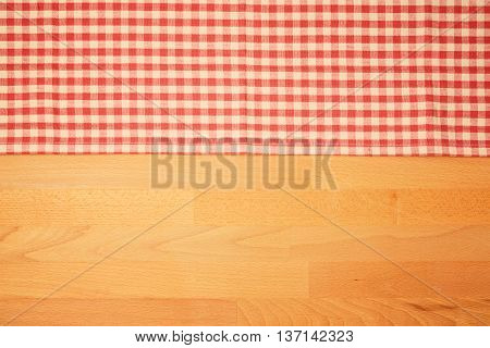 Kitchen background with checked tablecloth on wooden table. View from above
