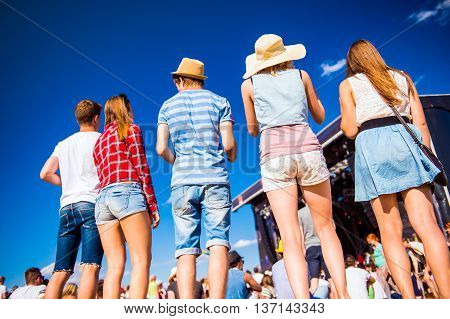 Group of teenagers at summer music festival, standing in front of stage, back view, rear, viewpoint