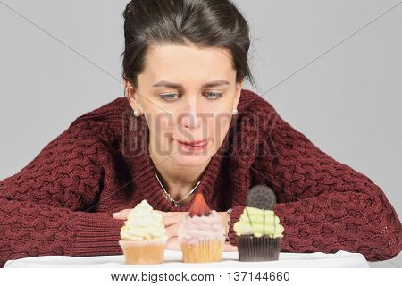 Half-length portrait of woman in burgundy sweater holding piece of tasty chocolate cake and looks with desire to eat this cake, on gray background