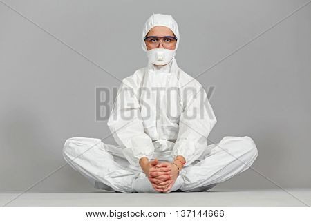 full portrait of woman in white protective suit of synthetic paper, glasses and respiritory half mask, sitting in lotus position, looking at  us, on gray background